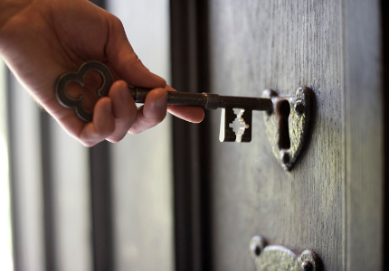 Male hand holding a large old fashioned key in front of the lock of an old wooden door